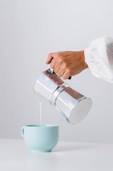 Despejando leite em um copo cerâmico