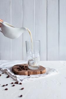 Despejando leite em um copo com gelo