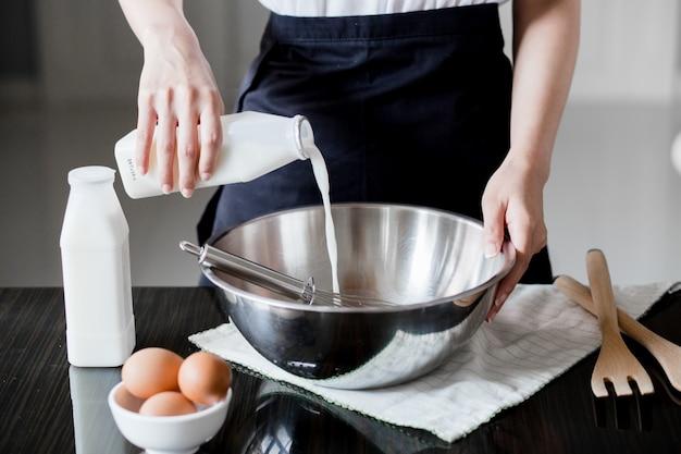 Despejando leite em uma tigela de farinha