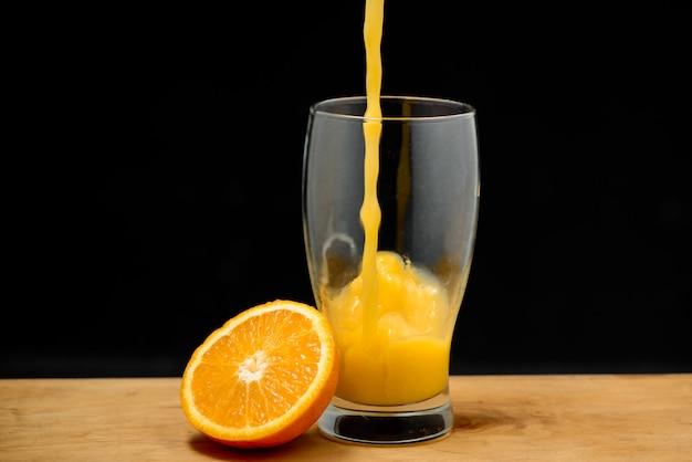 Despejando suco de laranja em vidro copie o espaço