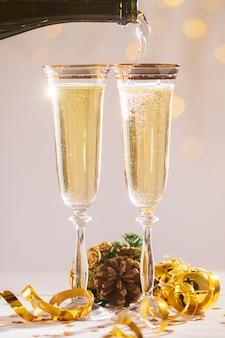 Despejando taças de champanhe em copos sobre pontos de desfoque de luz prontos para entrar no ano novo
