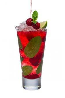 Despejar o suco de cereja ao coquetel alcoólico com limão e hortelã isolado no branco