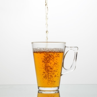 Despeje o chá saboroso em um copo de vidro.