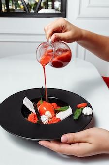 Despeje o molho de morango no sorvete com morangos frescos e decorado com hortelã.