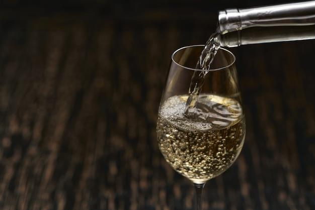 Despeje o vinho branco em um copo na mesa de madeira preta, close-up.