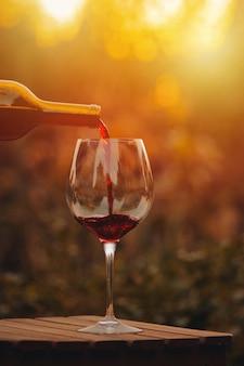 Despeje o vinho tinto. copo de vinho tinto na aldeia ao pôr do sol.