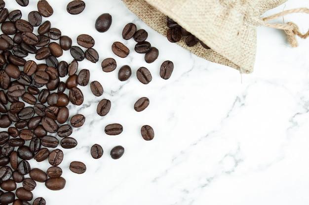 Despeje os grãos de café marrons em um saco de pano em um fundo de mármore com espaço de cópia. vista do topo.