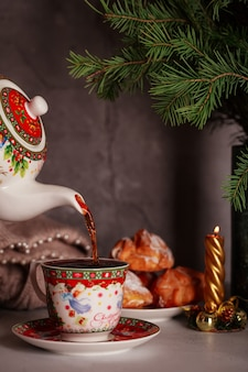 Despeje um chá delicioso de um bule de natal com bolos e galhos de pinheiro