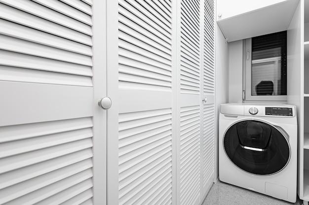 Despensa branca com guarda-roupa grande e máquina de lavar em apartamento novo de luxo