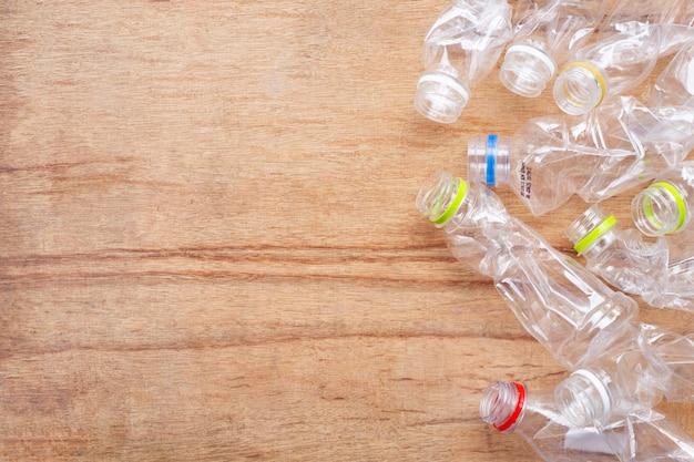 Desperdício do plástico, garrafas plásticas no fundo de madeira.