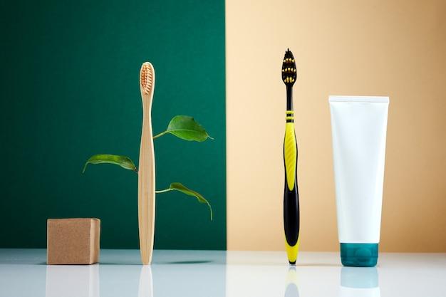 Desperdício zero, conceito criativo ecologicamente correto. escova de dentes de madeira em bambu com folhas vs escova de plástico. produto de beleza orgânico natural do banheiro. vida sem plástico.