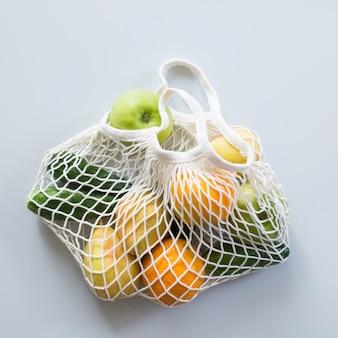 Desperdício zero. saco de rede moderno com frutas e legumes.