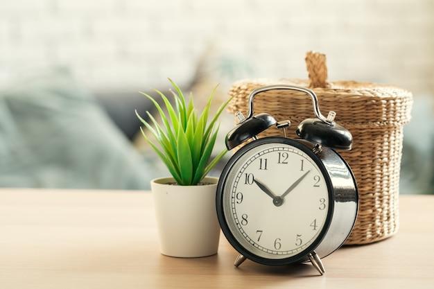 Despertador à moda antiga e planta de casa na mesa de madeira