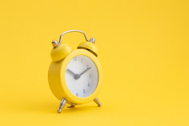 Despertador amarelo clássico sobre amarelo.
