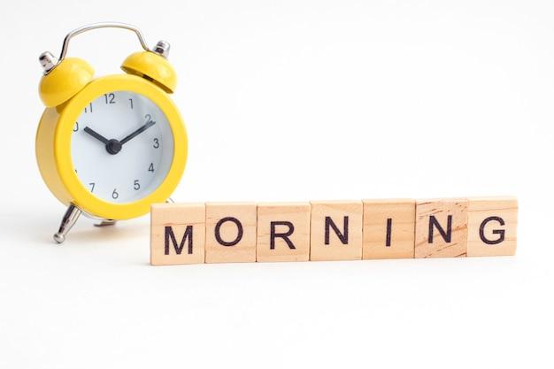 Despertador amarelo com sino e texto da manhã de cubos de madeira.
