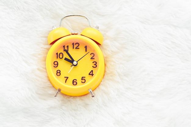 Despertador amarelo em lã branca. conceito de tempo tardio e preguiçoso