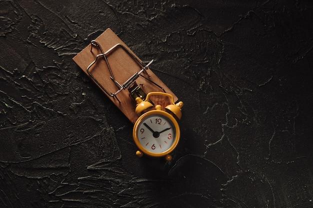 Despertador amarelo em uma ratoeira, conceito de armadilha do tempo.