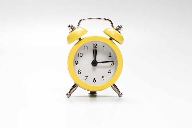 Despertador amarelo isolado em uma superfície branca.