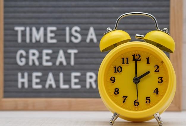 Despertador amarelo sobre uma placa com a hora da inscrição é um grande curador
