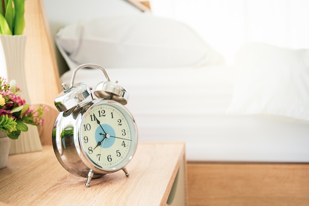 Despertador analógico na mesa de madeira no quarto