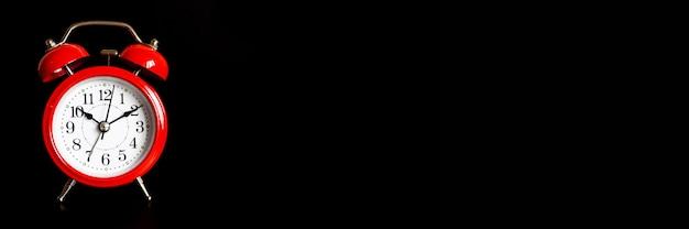 Despertador analógico redondo vermelho isolado no fundo preto.