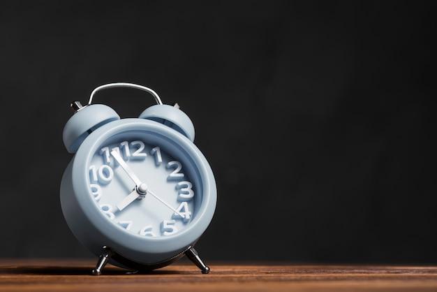 Despertador azul caindo na mesa de madeira contra o fundo preto