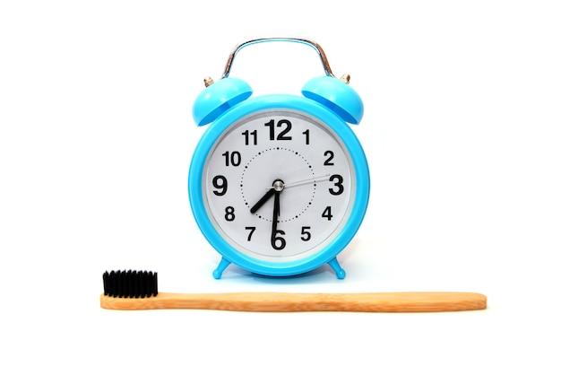 Despertador azul e escova de dentes de bambu isoladas no fundo branco. close-up. hora de escovar os dentes