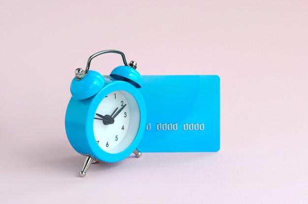 Despertador azul pequeno e cartão de crédito azul