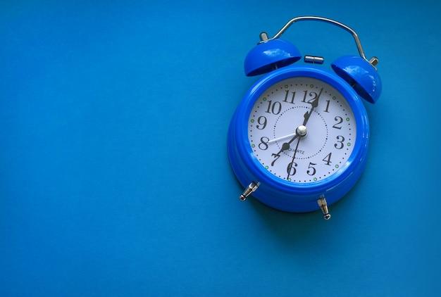 Despertador azul sobre fundo azul.