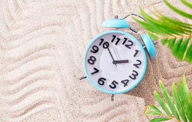 Despertador azul sobre fundo de areia, vista superior com espaço de cópia e folhas de palmeira verdes