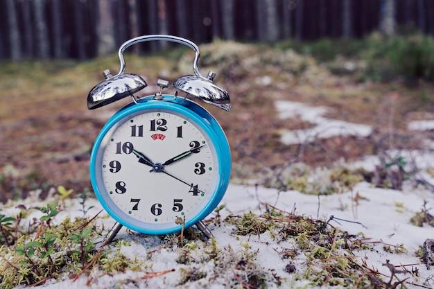Despertador azul vintage em fundo de floresta de inverno