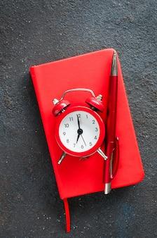 Despertador, bloco de notas e caneta