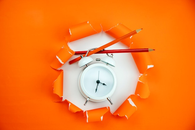 Despertador branco com lápis sobre fundo de papel aberto rasgado laranja
