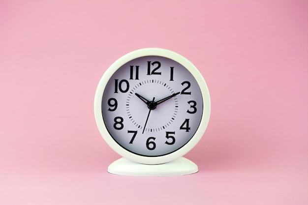 Despertador branco com números grandes no fundo cor-de-rosa.
