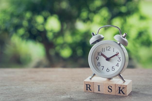Despertador branco do vintage colocado na palavra de madeira risco. o conceito de risco