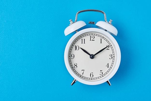 Despertador branco do vintage no backround azul com espaço da cópia. conceito de tempo