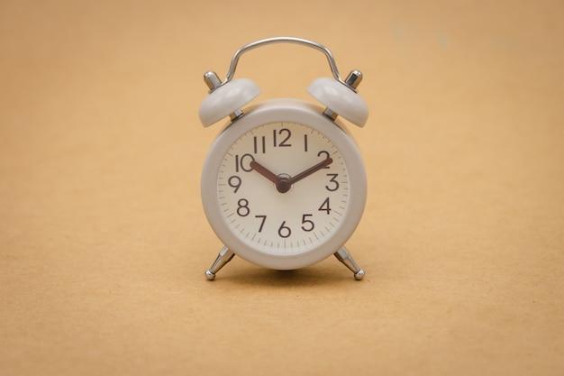 Despertador branco do vintage no conceito marrom do curso do fundo do tempo