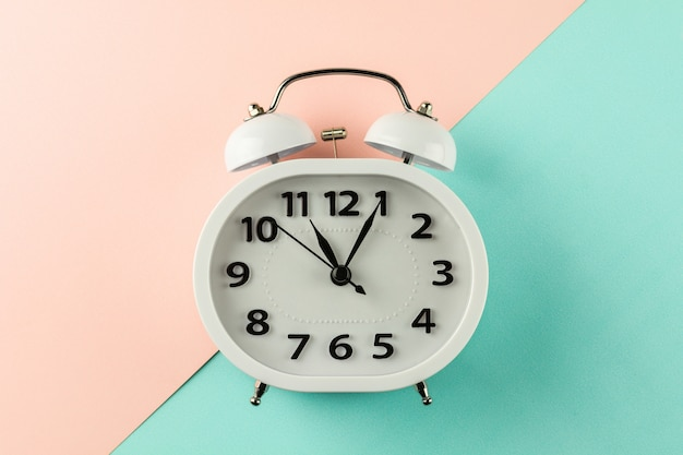 Despertador branco do vintage no fundo cor-de-rosa e azul.