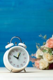 Despertador branco e flores rosa e rosa vermelha na mesa de madeira e fundo azul