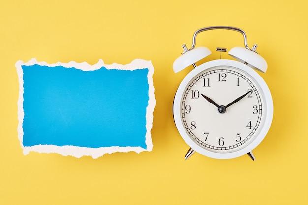 Despertador branco e folha de papel rasgada vazia em um fundo amarelo, vista superior. conceito de tempo