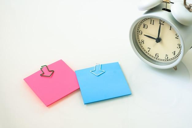 Despertador branco e notas auto-adesivas coloridas em um fundo branco