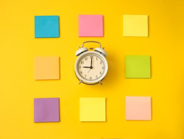 Despertador branco e notas auto-adesivas coloridas em uma tabela amarela. o conceito de tempo de trabalho. ambiente de trabalho