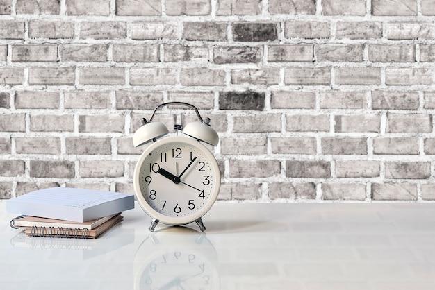 Despertador branco e notebook na mesa branca