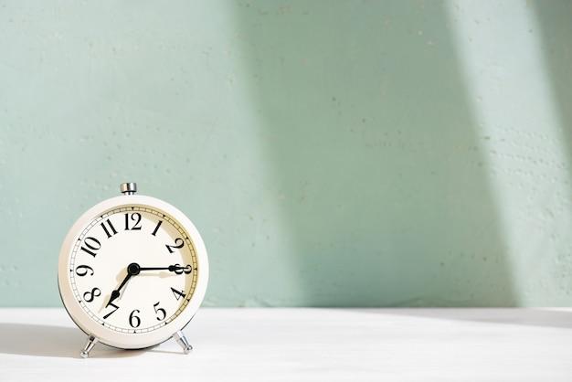 Despertador branco em cima da mesa contra a parede azul