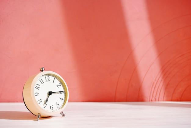Despertador branco em cima da mesa contra a parede laranja
