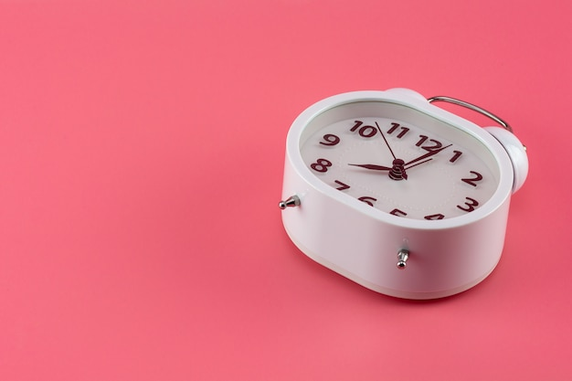 Despertador branco em rosa.