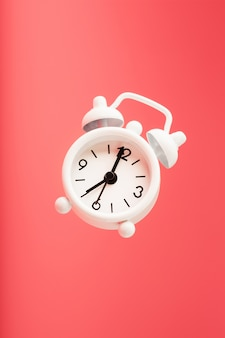 Despertador branco estilo retro em levitação isolado no fundo rosa.