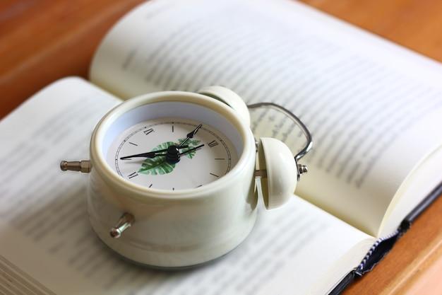 Despertador branco estilo retro em livro aberto na mesa