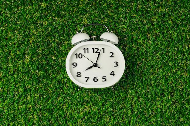 Despertador branco moderno no gramado da grama verde na manhã.
