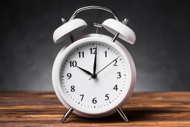 Despertador branco na mesa de madeira texturizada mostrando 10'oclock